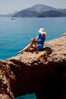 Mulher jovem curtindo férias na rocha com vista de luxo, caminhando e mostrando emoção no fundo do mar azul