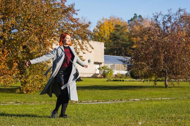 Mulher jovem curtindo o sol quente em um parque da cidade em um dia quente de outono