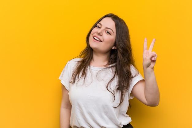 Mulher jovem curvilínea plus size alegre e despreocupada, mostrando um símbolo de paz com os dedos.