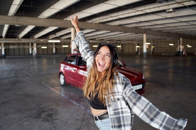 Mulher jovem dançando e pulando na frente de seu carro em um estacionamento. ela está feliz e louca.