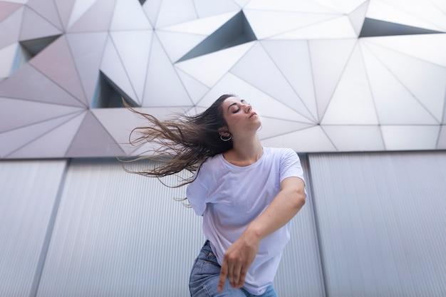 Mulher jovem dançando na rua com os olhos fechados e movendo o cabelo