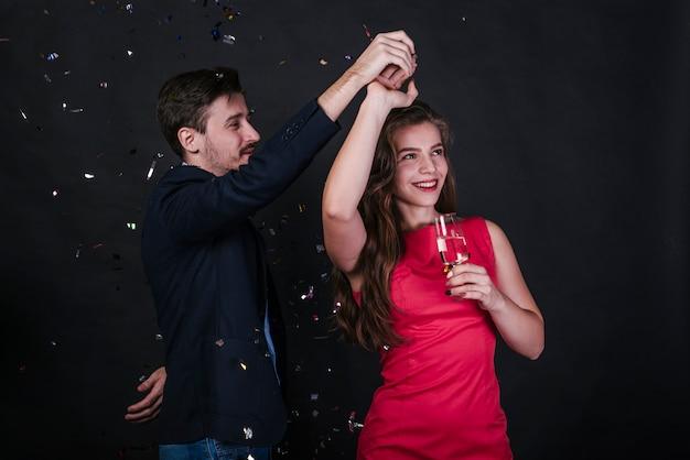 Mulher jovem, dançar, com, homem, com, vidro, de, bebida, entre, lançar confetti
