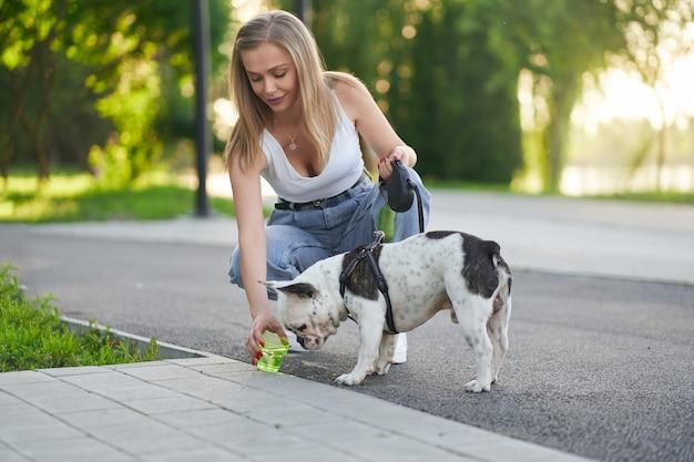 Mulher jovem dando água para cachorro no parque