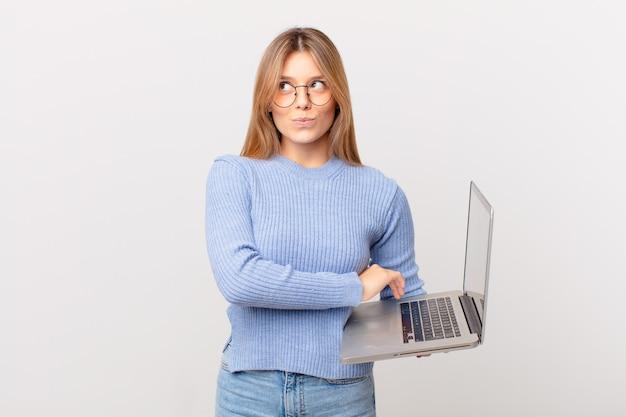 Mulher jovem dando de ombros com um laptop, sentindo-se confusa e insegura