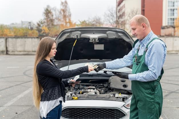 Mulher jovem dando dólares para um mecânico em serviço