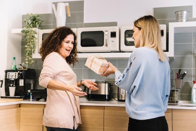 Mulher jovem, dar, presente, para, mãe, em, cozinha