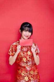 Mulher jovem de ano novo chinês usando cheongsam vermelho segurando um envelope