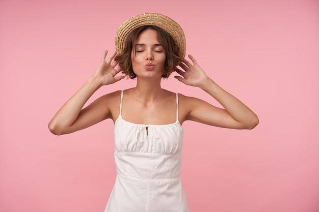 Mulher jovem de aparência agradável com corte de cabelo curto, mãos no chapéu de palha, olhos fechados e lábios dobrados no ar beijo, em um elegante vestido branco