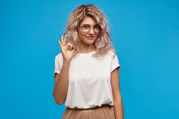 Mulher jovem de aparência amigável e positiva com cabelo encaracolado rosado e sorriso fofo e confiante