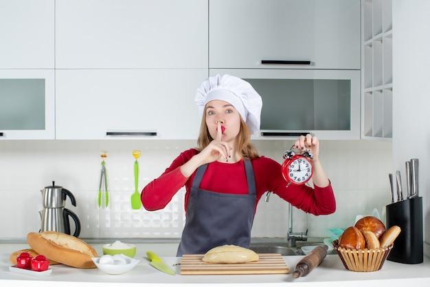Mulher jovem de avental segurando um despertador vermelho fazendo sinal de silêncio na cozinha de frente