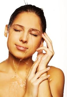 Mulher jovem de beleza com gotas de água no rosto puro - isolado no branco