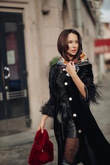 Mulher jovem de beleza elegante em roupas da moda, caminhar ao ar livre no centro da cidade. linda menina morena elegante com uma capa preta posando rodeada pelo exterior do edifício