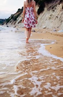 Mulher jovem de beleza em um vestido elegante, andando descalço na praia, deixando pegadas na areia ao pôr do sol no horizonte. conceito de viagens e férias.
