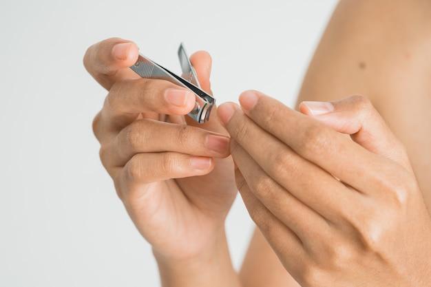 Mulher jovem de beleza fazendo manicure com cortar a unha sobre a parede branca conceito de cuidados saudáveis.