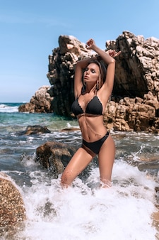 Mulher jovem de biquíni preto na praia