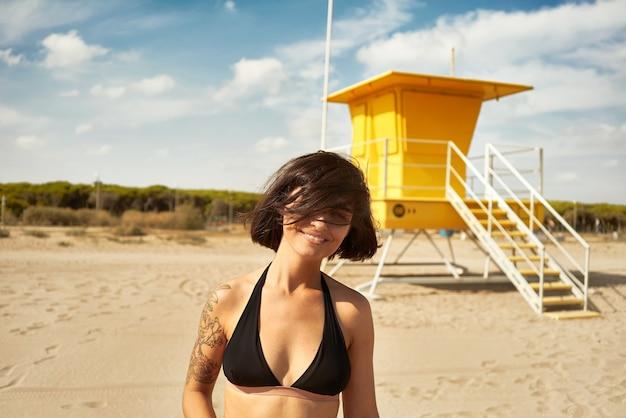 Mulher jovem de biquíni preto perto de um posto de salva-vidas amarelo