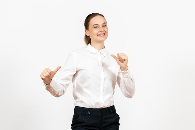 Mulher jovem de blusa branca com expressão animada na luz de fundo branco trabalho de escritório emoção feminina de frente