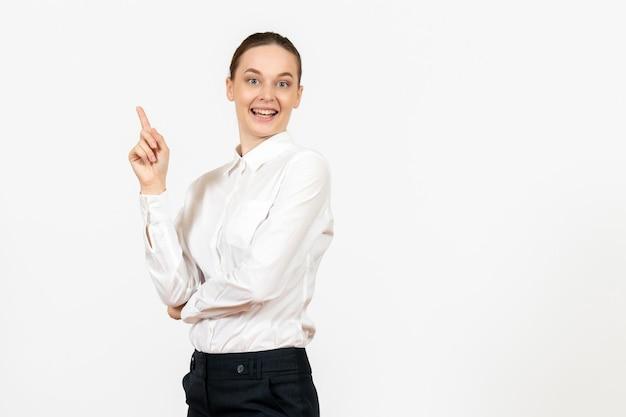 Mulher jovem de blusa branca com rosto animado sobre fundo branco claro.