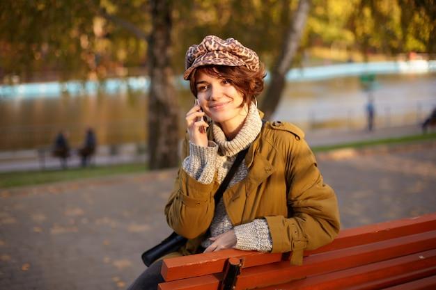 Mulher jovem de cabelo castanho positivo com aparência agradável e penteado casual, tendo uma bela conversa ao telefone, enquanto está sentado no banco de madeira no parque da cidade e sorrindo com prazer