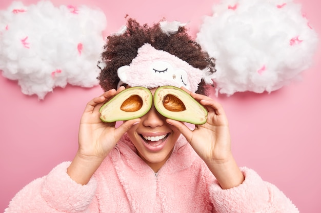 Mulher jovem de cabelo encaracolado positiva cobre os olhos com metades de abacate faz procedimentos de beleza em casa, vestida com roupas de dormir quentes e com uma venda isolada sobre a parede rosa