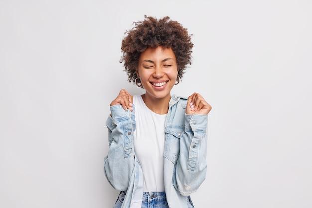 Mulher jovem de cabelo encaracolado positiva levanta as mãos, aguarda resultados, alegra-se, notícia incrível mantém os olhos fechados sorrisos amplamente usa camisa jeans isolada sobre a parede branca