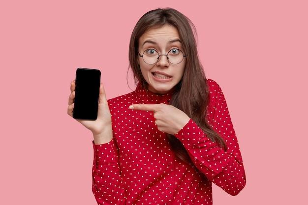 Mulher jovem de cabelo escuro e perplexa usando óculos ópticos, aponta para um dispositivo eletrônico com tela simulada, usa camisa vermelha, anuncia um novo dispositivo, tem olhos verdes