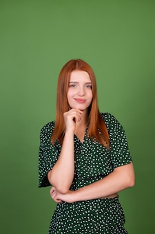 Mulher jovem de cabelo ruivo na parede verde questionando ponderadamente