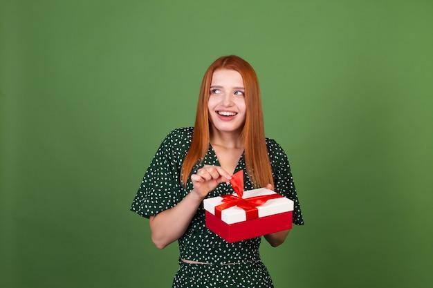 Mulher jovem de cabelo vermelho na parede verde com caixa de presente feliz animada surpresa surpresa