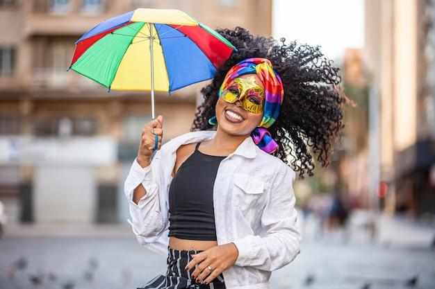 Mulher jovem de cabelos cacheados comemorando a festa de carnaval brasileira com guarda-chuva de frevo na rua.