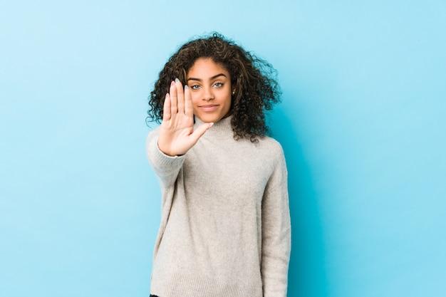 Mulher jovem de cabelos cacheados em pé com a mão estendida, mostrando o sinal de stop