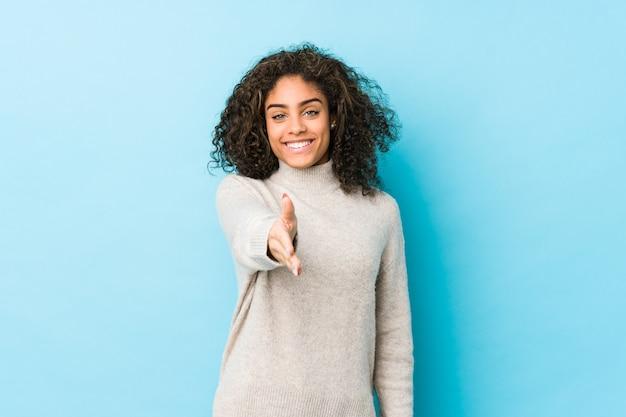 Mulher jovem de cabelos cacheados, esticando a mão na câmera em gesto de saudação