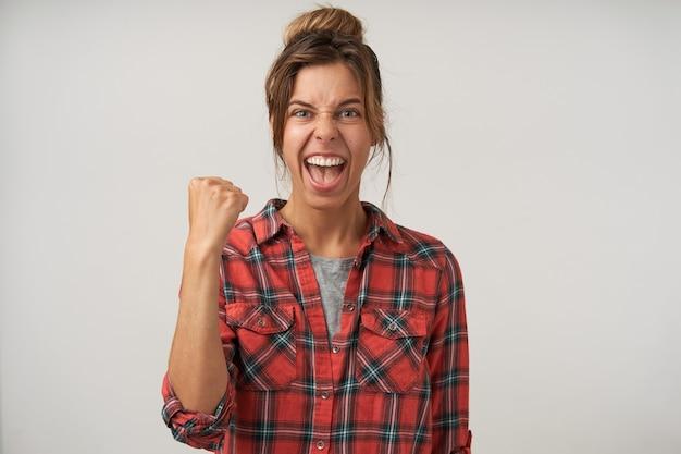 Mulher jovem de cabelos castanhos animada com penteado coque levantando o punho em um gesto de sim enquanto olha emocionalmente para a câmera com a boca aberta, posando sobre fundo branco