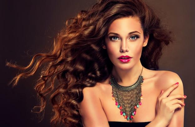 Mulher jovem, de cabelos castanhos, cabelos longos e volumosos com excelentes ondas.