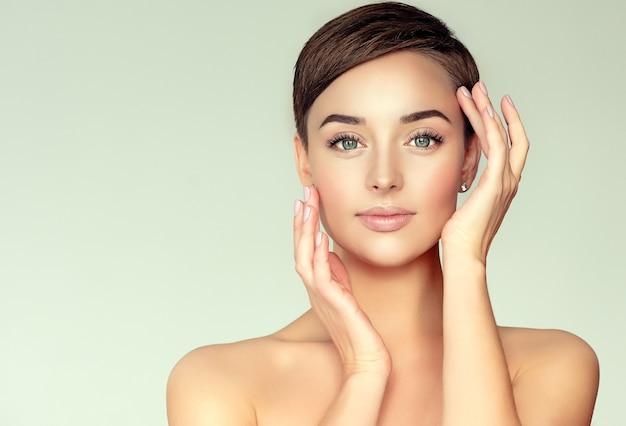 Mulher jovem, de cabelos castanhos, com corte de cabelo curto e elegante e pele limpa, fresca.