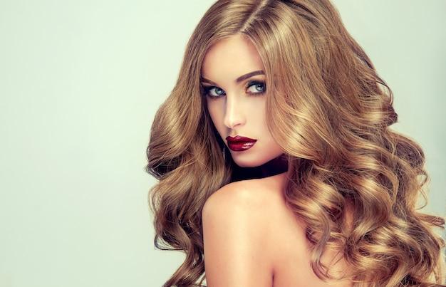 Mulher jovem, de cabelos castanhos e cabelos volumosos. linda modelo com penteado comprido, denso e cacheado e maquiagem viva. cabelo perfeito. cabelo incrivelmente denso, ondulado e brilhante.