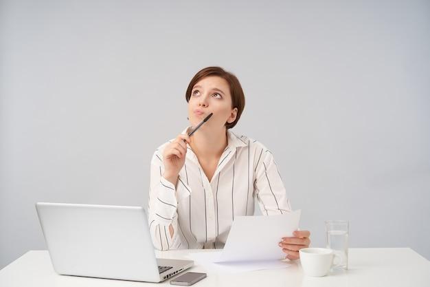 Mulher jovem de cabelos castanhos perplexa com um corte de cabelo curto e moderno, mantendo o papel e a caneta nas mãos levantadas enquanto olha pensativamente para cima, posando em branco