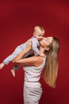 Mulher jovem de cabelos compridos no vermelho, segurando o filho nos braços e beijando suavemente sua bochecha.