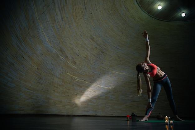 Mulher jovem de cabelos compridos praticando ioga em uma sala esférica e fazendo pose de triângulo com uma mão para cima