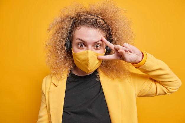 Mulher jovem de cabelos encaracolados positiva faz gesto de paz sobre o olho usa máscara protetora enquanto visita lugares públicos vestidos com roupas formais elegantes ouve música através de fones de ouvido. vida durante a quarentena