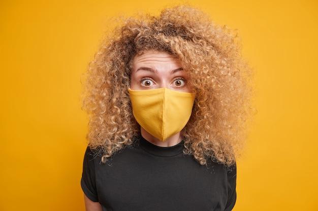 Mulher jovem de cabelos encaracolados surpresa olha fixamente e usa máscara protetora amarela incentiva a ficar segura durante o surto de coronavírus vestida em poses de camiseta preta interiores. conceito de distanciamento social