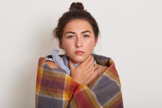 Mulher jovem de cabelos escuro doente com coque na cabeça, posando isolado sobre o estúdio branco