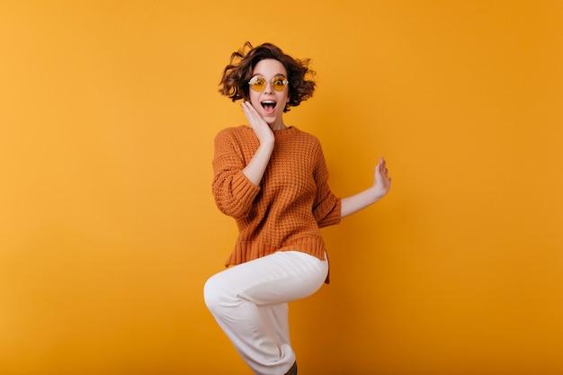 Mulher jovem de cabelos escuros pulando e expressando felicidade. retrato de menina positiva surpresa com corte de cabelo curto e tatuagem de braço dançando com um sorriso.