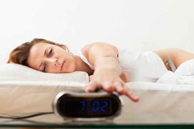 Mulher jovem de cabelos ruivos cansada na parte da manhã desligando o despertador