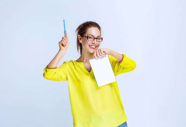 Mulher jovem de camisa amarela mostrando os resultados do teste e os erros nele