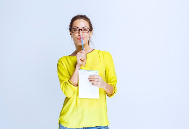 Mulher jovem de camisa amarela segurando sua folha de exame e pensando enquanto segura uma caneta