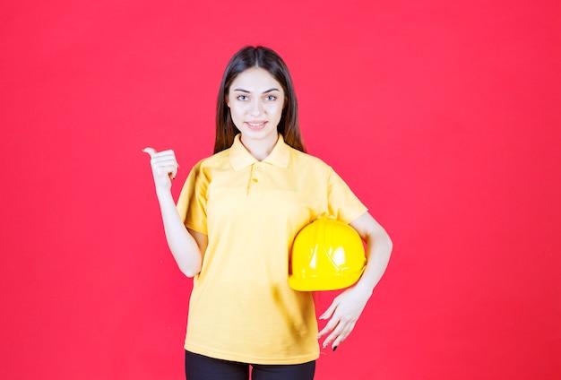 Mulher jovem de camisa amarela segurando um capacete amarelo e apontando para alguém atrás
