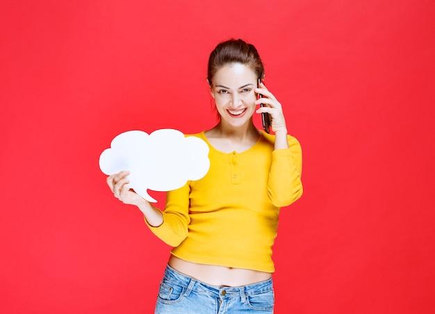 Mulher jovem de camisa amarela segurando um quadro de informações em forma de nuvem e falando ao telefone