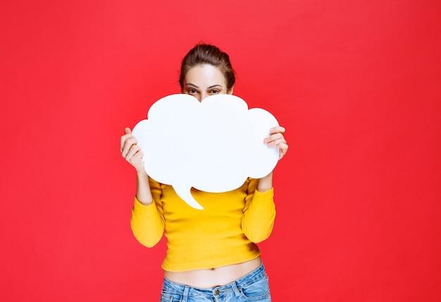 Mulher jovem de camisa amarela segurando um quadro de informações em forma de nuvem