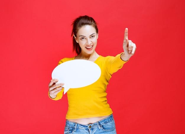 Mulher jovem de camisa amarela segurando um quadro oval de informações e levantando o dedo para chamar a atenção