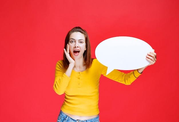 Mulher jovem de camisa amarela segurando um quadro oval de informações, parecendo confusa e pensativa